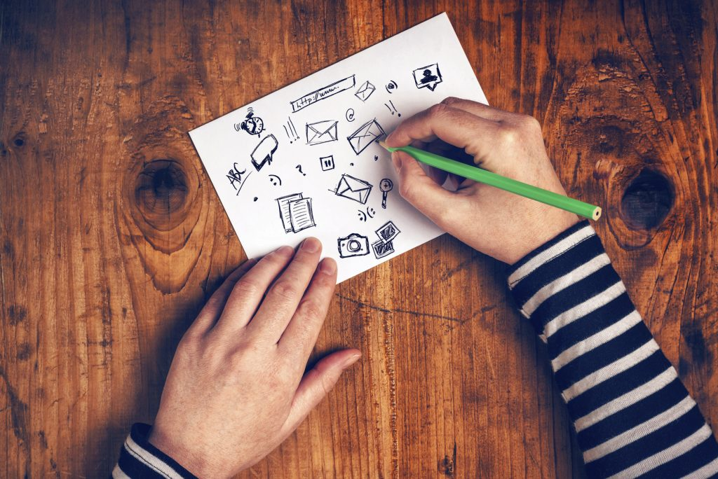 Female graphic designer sketching software icons on paper